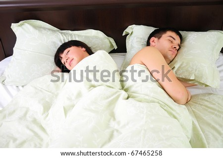 Young couple sleeping together in one bed. - stock photo