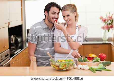 Young couple slicing pepper in their kitchen - stock photo
