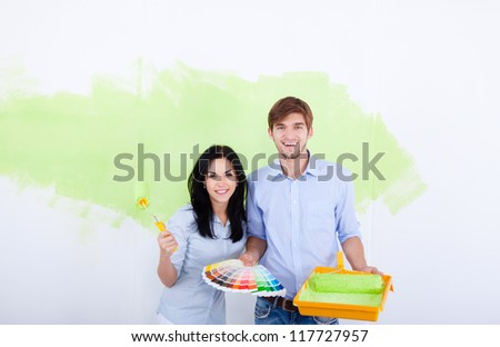 young couple smile choose palette color pantone paint in green color white wall of their new apartment home - stock photo