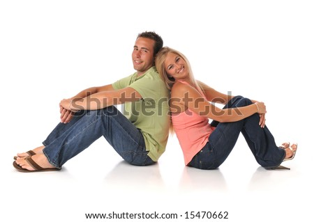 Young couple smiling and sited isolated on a white background - stock photo