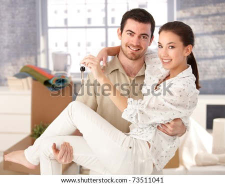 Young couple smiling happily in new house, holding keys in hand, mess around. - stock photo