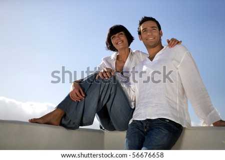 Young couple smiling on a terrace - stock photo