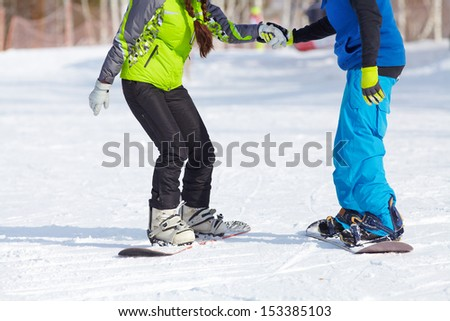 Young couple snowboarders in a ski resort. unrecognizable - stock photo