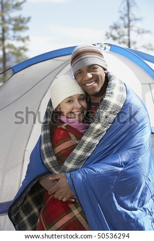 Young couple standing at campsite, wrapped in blankets. - stock photo