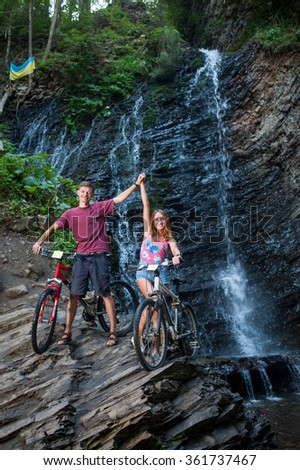 Young couple standing by waterfall and holding hands up near their bikes.Full length portrait - stock photo