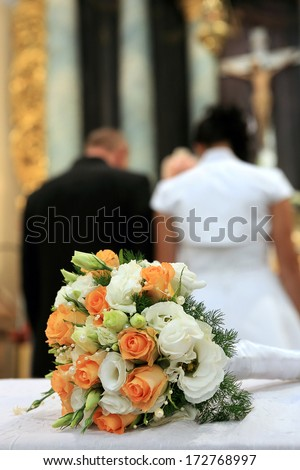 Young couple standing in front of the altar during the wedding ceremony - stock photo