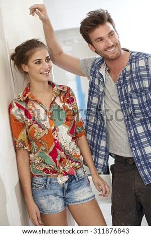 Young couple standing in home under construction, smiling. - stock photo
