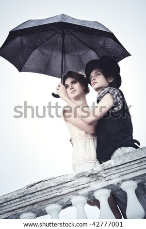Young couple standing in the rain. Soft blue tint. - stock photo