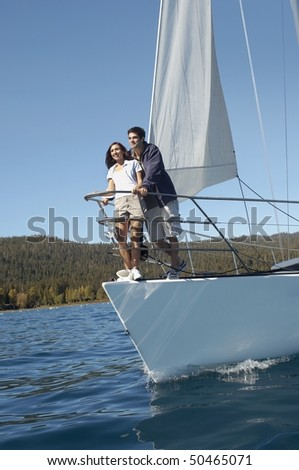 Young couple standing on bow of sailboat - stock photo