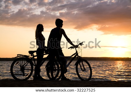 Young couple standing on seashore with their bicycles and admiring sunset - stock photo