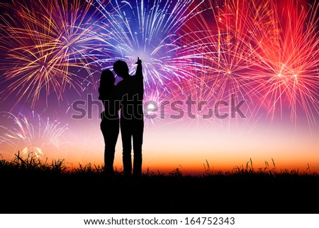 young couple standing on the hill and watching the fireworks  - stock photo