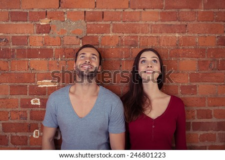 Young couple standing side by side against a brick wall watching something in the air with smiles of pleasure - stock photo