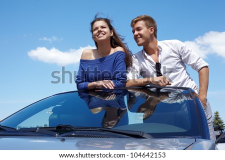 Young couple stands in cabriolet leaning their elbows on windshield, smiles and talks - stock photo