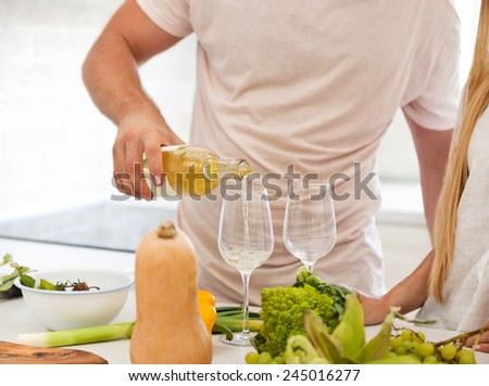 Young couple starting to drink a white wine at home - stock photo