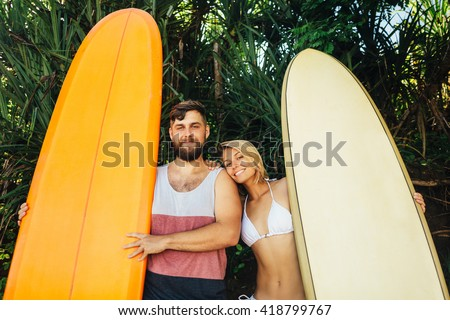 Young couple stay on tropical beach with their surfboards and smile. Surf couple - stock photo