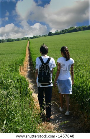 Young couple strolling through farmland on a summers day - stock photo