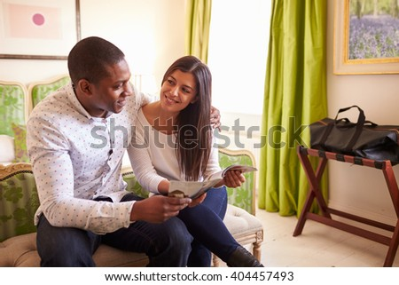 Young couple study a guide brochure together in a hotel room - stock photo