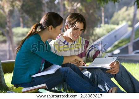Young couple studying outdoors, side view - stock photo