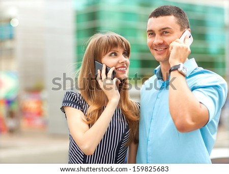 Young couple successful businessmen agree on the best deal. He was talking on the phone, it searches the internet for new business partners. - stock photo