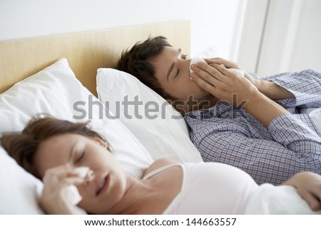 Young couple suffering from colds in bed - stock photo