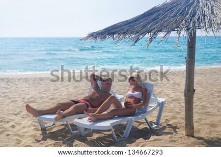 Young couple sunbathe in longue on the sea beach under sunshade - stock photo