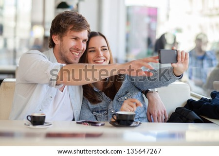 Young couple taking a photo of themselves in a cafe - stock photo