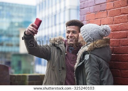 Young couple taking a selfie in the city. - stock photo