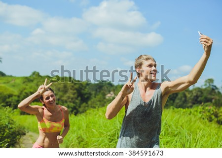 Young couple taking a selfie with a smartphone before working out together in a running track - stock photo