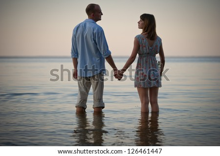 young couple taking a walk on beach in the evening - stock photo
