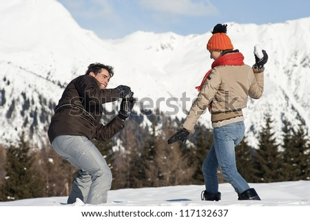 Young couple taking photos on the snow - stock photo