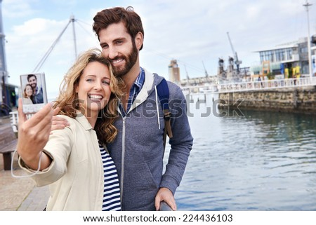 young couple taking selfi on vacation at the waterfront area near the ocean - stock photo