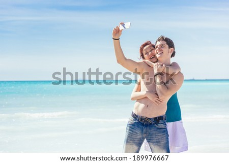 Young Couple Taking Selfie at Beach - stock photo