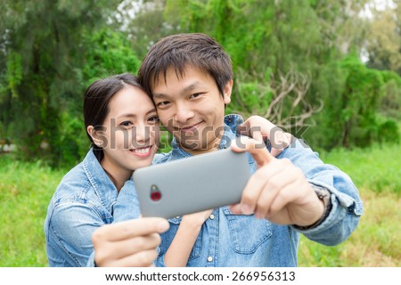 Young Couple Taking Selfie at Park - stock photo