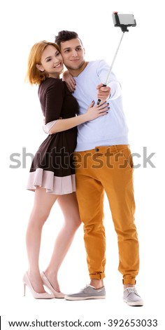 Young couple taking selfie with mobile phone isolated on white - stock photo