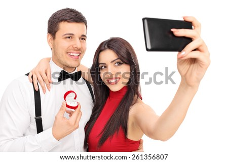 Young couple taking selfie with their engagement ring isolated on white background - stock photo
