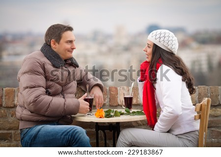 Young couple talking and having mulled wine - stock photo