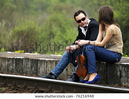 Young couple talking in a railway station - stock photo