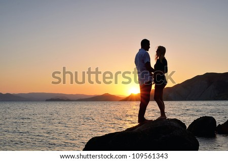 Young couple talking on the beach with the setting sun - stock photo