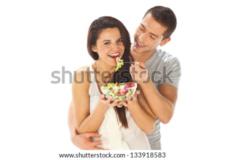 Young couple tasting a salad. Happy couple eating salad together on a white background - stock photo
