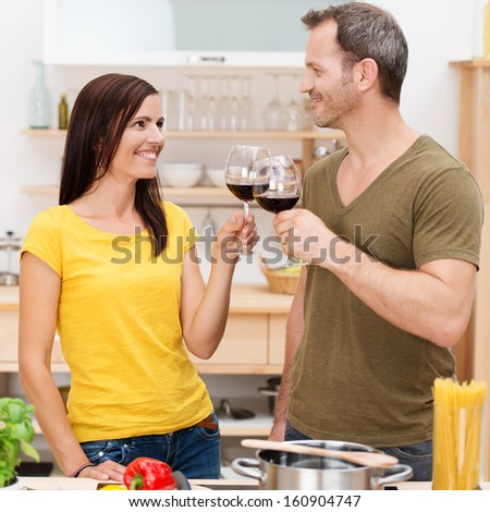 Young couple toasting each other with glasses of red wine as they stand together in the kitchen preparing a healthy meal - stock photo