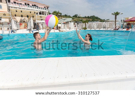 Young couple tossing a beach ball to each other as they frolic around in a cool blue inviting swimming pool at a summer resort - stock photo