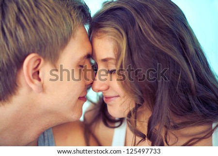 Young couple touching by their faces - stock photo
