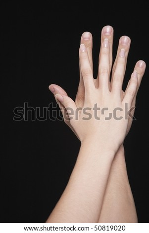Young couple touching palms, arms raised together, close-up on hands - stock photo