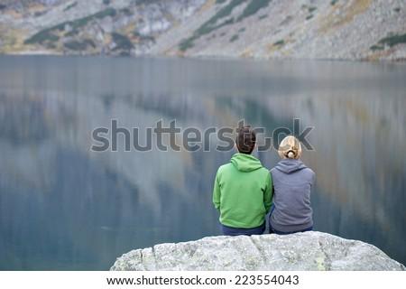Young couple tourist looking at mountain lake, High Tatra Mountains, Poland, Slovakia - stock photo