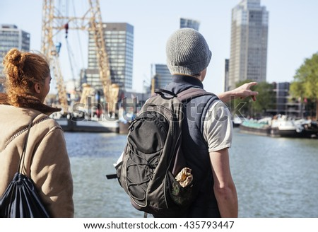 Young couple tourists looking and pointing to Rotterdam city harbour, future architecture concept, industrial lifestyle - stock photo