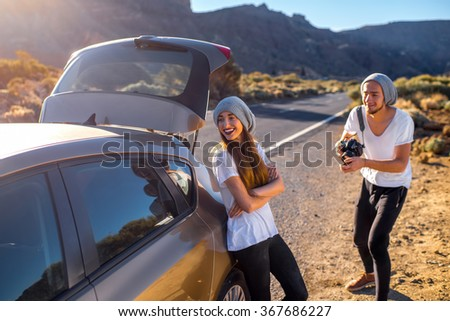 Young couple travelers in white t-shirts and gray hats having fun being photographed with professional photo camera near the car on the road. - stock photo