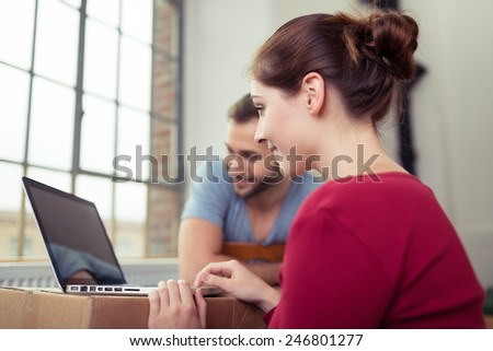 Young couple using a laptop on a cardboard box as they connect with their friends on social media during a move to a new home - stock photo