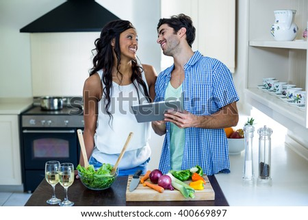 Young couple using digital tablet in kitchen at home - stock photo