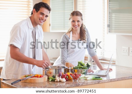 Young couple using notebook to look up recipe - stock photo
