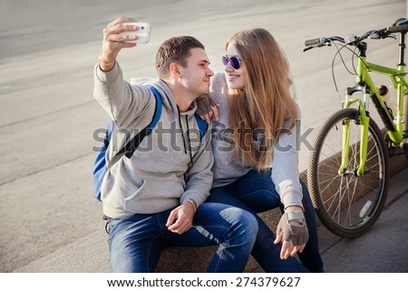 young couple using smart phone for selfie in the city - stock photo